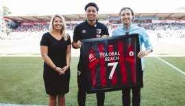 AFC Bournemouth Partnerships Manager Amy Marks and new signing Anaut Danjuma present a commemorative shirt to Joseph Stevens of Global Reach to mark the company's arrival as an official corporate supporter and supplier of the Cherries as well as an official partner of the club's commercial arm AFC Business